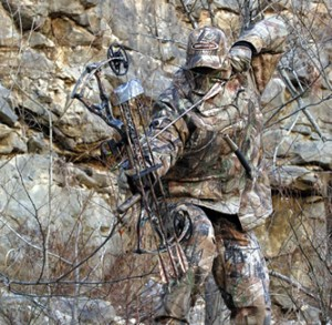 man in camo hunting with bow