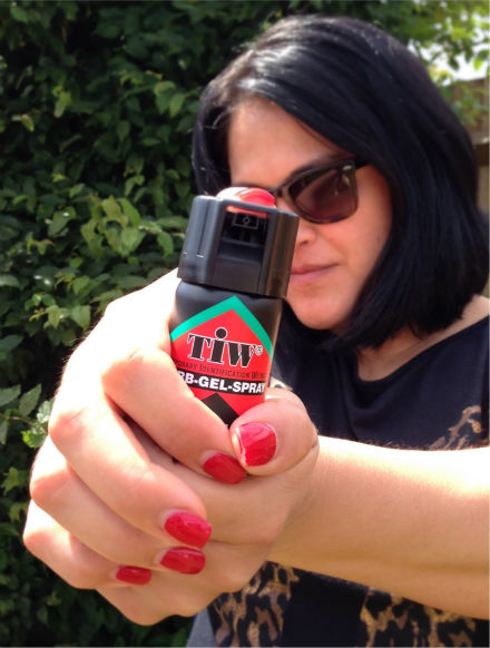 girl with can of legal pepper spray for the Uk
