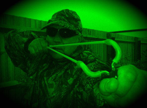 man shooting catapult night vision