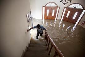 man walking up stairs in flooded house